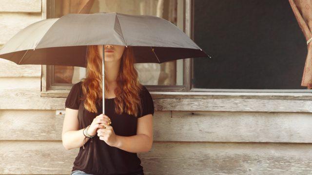 Nuori nainen seisoo auringossa pidellen päivänvarjoa kädessään.
