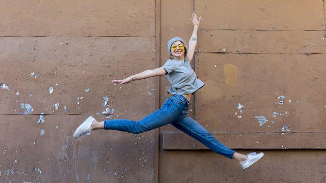 Farkkuihin pukeutunut tyttö hyppää iloisena ilmaan.