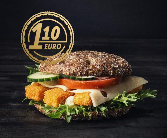 Kuvassa on tummaa taustaa vasten ruishampurilainen jonka täytteenä on kolme kalapuikkoa, juustoa, tomaattia, kurkkua, salaattia sekä kastike.