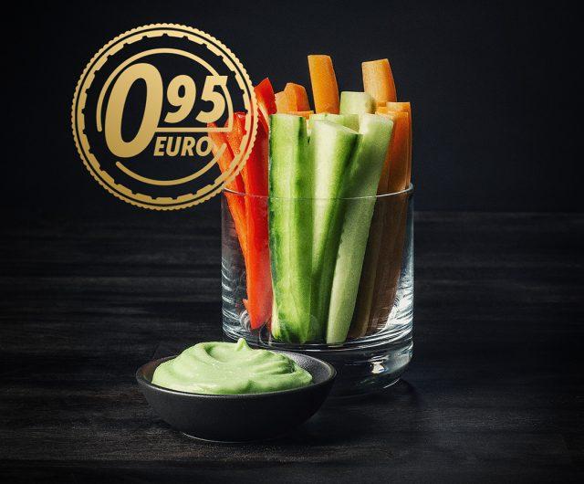 Kuvassa on tummaa taustaa vasten lasissa dippivihanneksia, kurkkua, porkkanaa sekä paprikaa. Lasin edessä pienessä kulhossa on wasabi-kermaviili kastiketta.